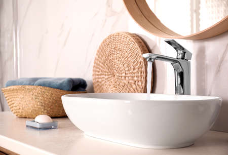 Lavabo con agua corriente en el elegante interior del baño Foto de archivo