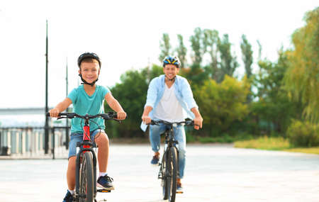 Dad and son riding bicycles together outdoors 版權商用圖片