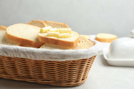 Slices of tasty fresh bread with butter in wicker basket on light marble table
