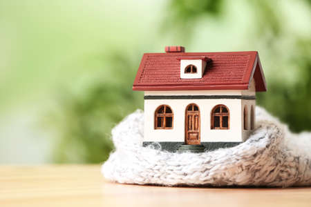 House model and scarf on wooden table against blurred background, space for text. Heating efficiency