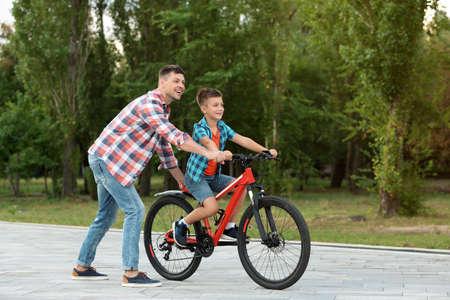 Dad teaching son to ride bicycle in park 版權商用圖片