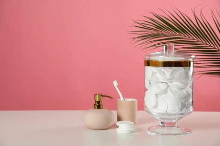 Jar with cotton pads on white table against pink background. Space for text Stock Photo