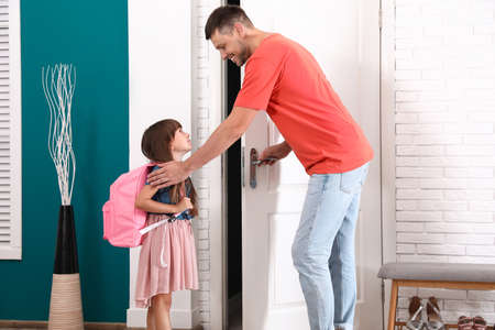Happy father and little child with school bag in hallway