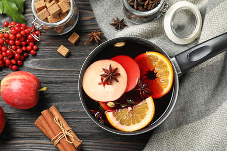 Saucepan with tasty mulled wine on black wooden table, flat lay Stock Photo