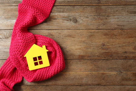 House model and scarf on wooden background, top view with space for text. Heating efficiency Reklamní fotografie