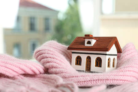 House model and pink scarf on table on blurred background, space for text. Heating efficiency Reklamní fotografie