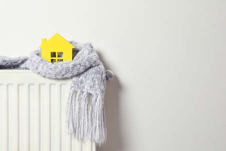 House model wrapped in scarf on radiator indoors, space for text. Winter heating efficiency Stock Photo