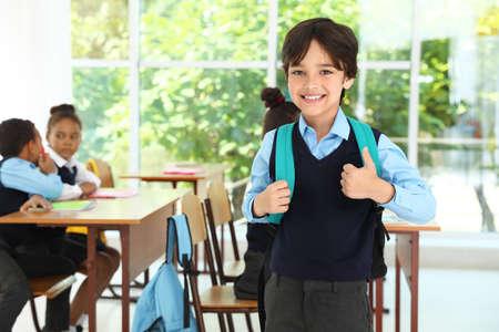 Boy wearing school uniform with backpack in classroom