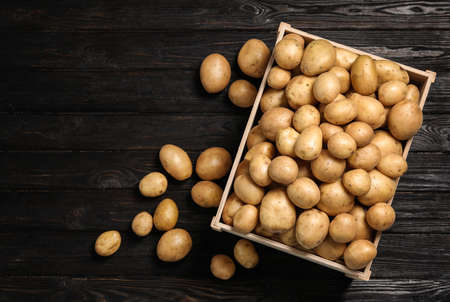 Raw fresh organic potatoes on black wooden background, top view Banco de Imagens