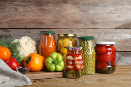 Glass jars with pickled vegetables on wooden table against brown background Banco de Imagens