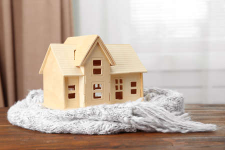 House model and scarf on wooden table indoors. Heating efficiency