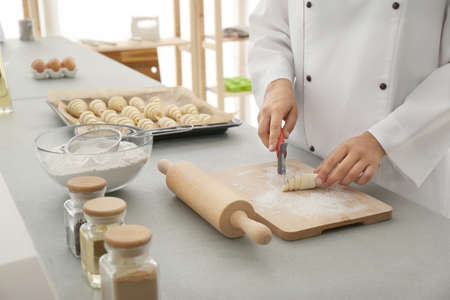 Female pastry chef preparing croissant at table in kitchen, closeup