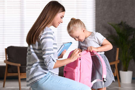 Young mother and little child putting textbooks into school bag at home
