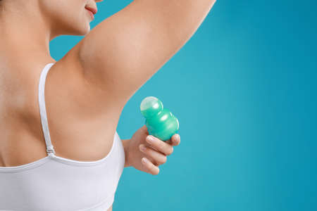 Young woman applying deodorant to armpit on teal background, closeup