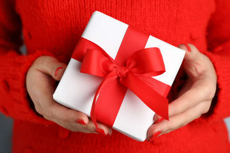 Young woman holding Christmas gift, closeup view Stock Photo