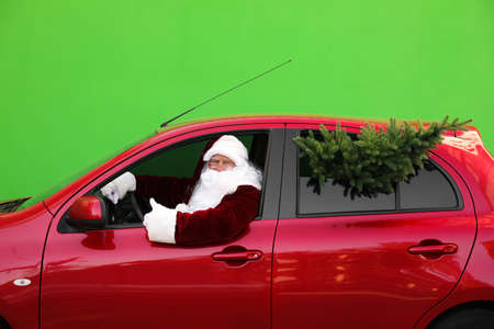 Authentic Santa Claus with fir tree driving car against green background