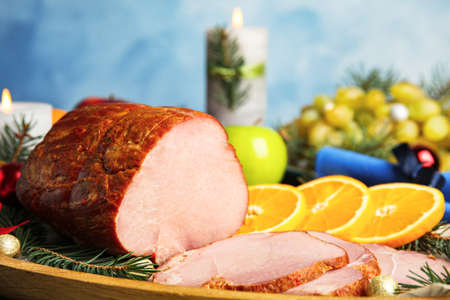 Delicious ham served on wooden tray, closeup. Christmas dinner