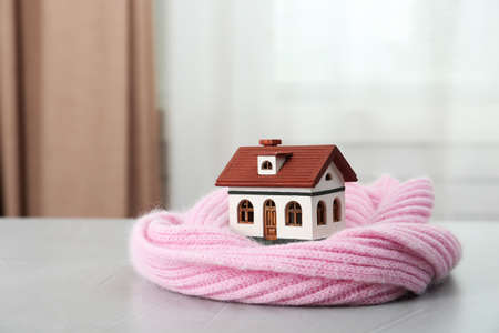 Wooden house model and scarf on grey table indoors. Heating efficiency