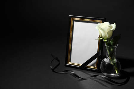 Funeral photo frame with ribbon and white rose on black background. Space for design Stock Photo