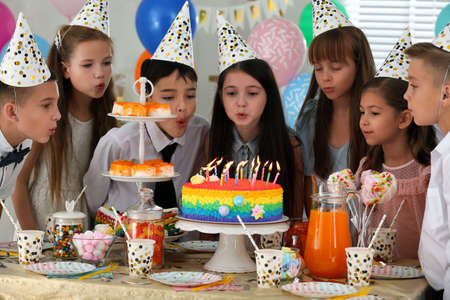 Happy children blowing out candles on cake at birthday party indoors Stock fotó