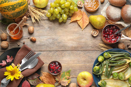 Frame made of autumn vegetables, fruits and cutlery on wooden background, flat lay with space for text. Happy Thanksgiving day