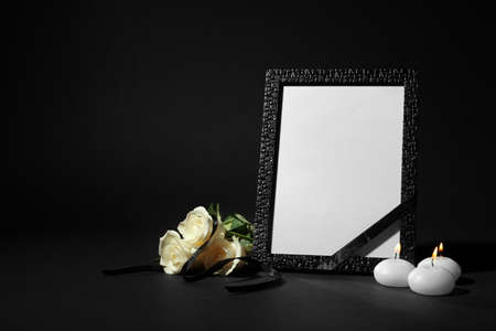 Funeral photo frame with ribbon, white roses and candles on black background. Space for design