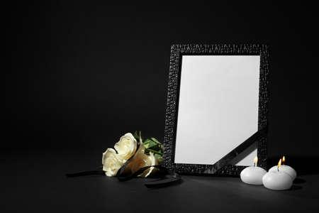 Marco de fotos funerario con cinta, rosas blancas y velas sobre fondo negro. Espacio para el diseño