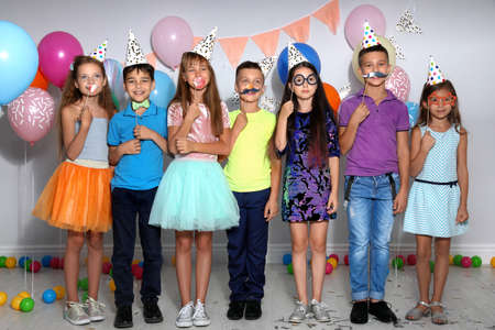 Happy children with photo booth props at birthday party indoors Stock fotó