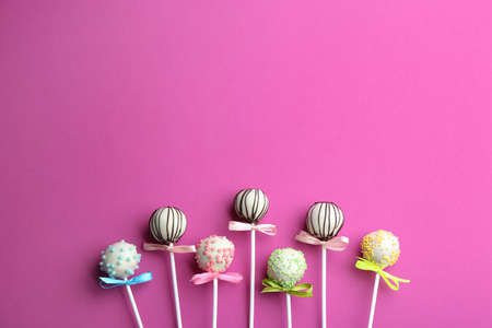 Different tasty cake pops on pink background, flat lay. Space for text