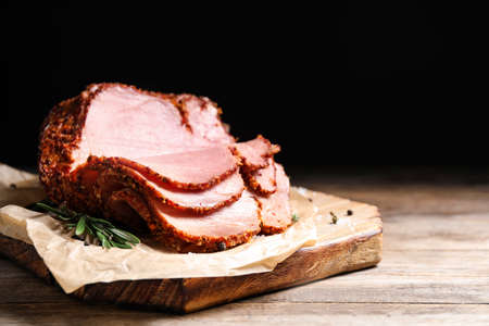 Delicious ham on wooden table against black background, space for text. Christmas dinner