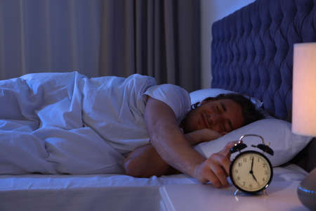 Sleepy young man turning off alarm clock on nightstand. Bedtime