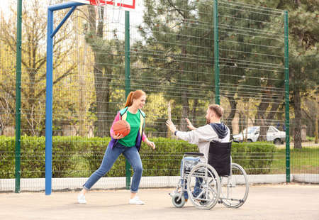 Man in wheelchair and young woman playing basketball on sports ground Imagens