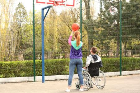 Hombre en silla de ruedas y mujer joven jugando baloncesto en el campo de deportes Foto de archivo