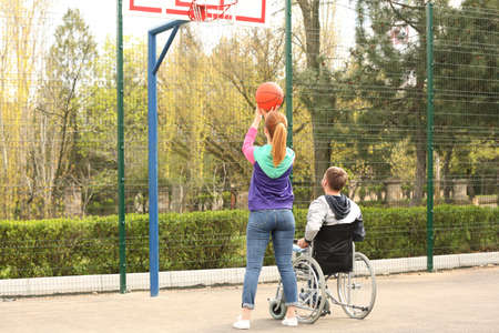 Man in wheelchair and young woman playing basketball on sports ground