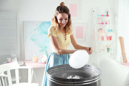 Young woman making cotton candy using modern machine in room Reklamní fotografie