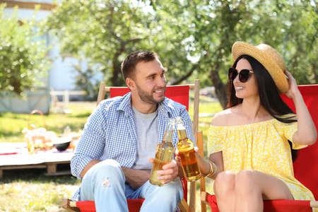 Smiling friends clinking bottles on picnic in park on summer day