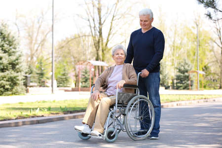 Senior woman in wheelchair and mature man at park on sunny day