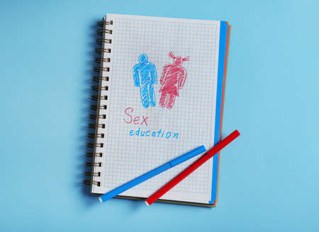 Notebook with phrase SEX EDUCATION on blue background, top view Stock Photo