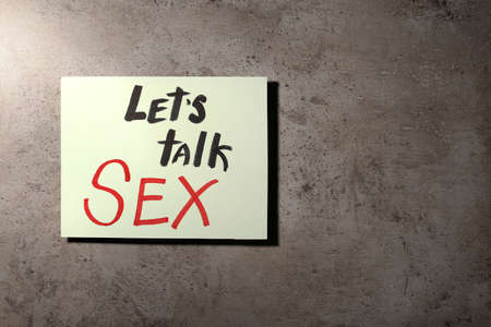 Note with phrase LETS TALK SEX on stone background, top view Stock Photo