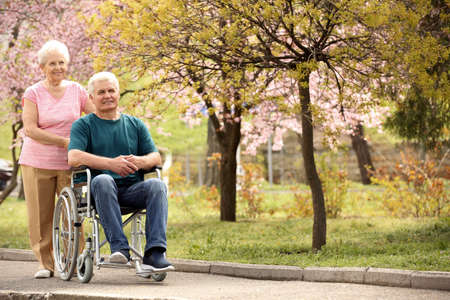 Senior man in wheelchair and woman at park on sunny day