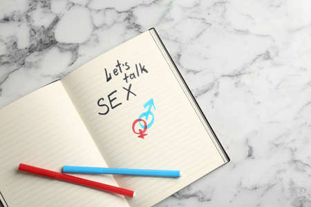 Notebook with phrase LETS TALK SEX and gender symbols on marble background, top view