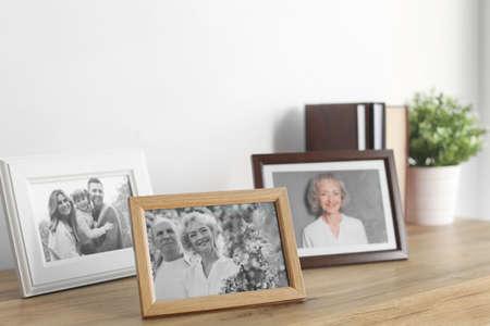 Framed photos on cabinet near white wall Stock fotó