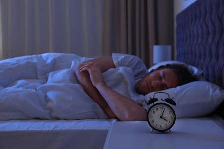 Wecker auf Nachttisch in der Nähe des schlafenden jungen Mannes. Bettzeit Standard-Bild