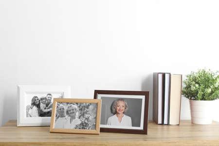 Fotos enmarcadas en el gabinete cerca de la pared blanca. Espacio para texto Foto de archivo