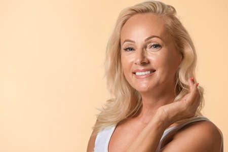 Portret van mooie rijpe vrouw met perfecte huid op beige achtergrond. Ruimte voor tekst