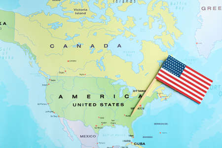 Little national flag near USA on world map, top view
