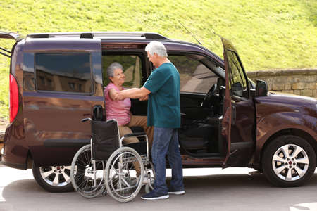 Mature man helping senior woman to get out from van into wheelchair outdoors