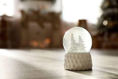 Snow globe with deer and trees on wooden floor, space for text Imagens