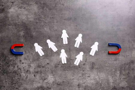 Magnet attracting paper people on grey stone background, flat lay. Marketing concept Stok Fotoğraf