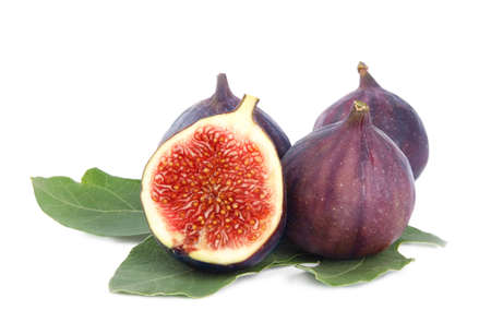 Fresh juicy purple figs and green leaves on white background